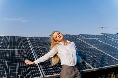 Woman leans on solar panels. Blonde dressed white formal shirt on the power plant. Free electricity for home. Green energy. Solar cells power plant business.