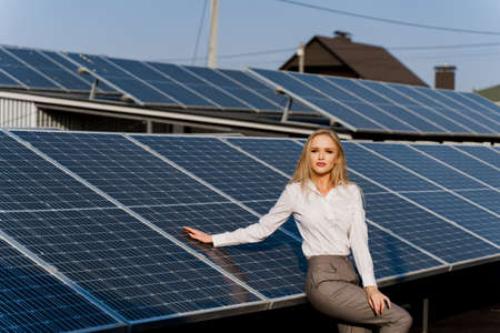 Girl and solar panels stands in row on the ground at sunset. Woman dressed white formal shirt on the power plant. Free electricity for home. Green energy. Solar cells power plant business.