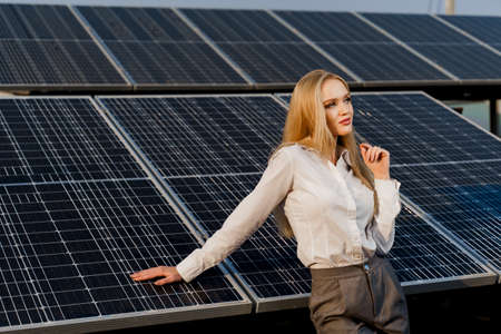 Blonde model with solar panels stands in row on the ground. Girl dressed white formal shirt smiles on the power plant. Free electricity for home. Green energy. Solar cells power plant business. Banco de Imagens