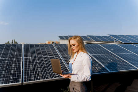 Investor and solar panels. Blonde woman with laptop near blue solar panels row on the ground Girl weared formal white shirt. Free electricity for home. Sustainability of planet. Green energy.