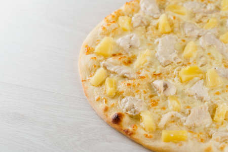 Hawaiian pizza with pineapple, chicken, cheese and sauce isolated on white wooden background. Advert for social network of restaurants, caffee. Promotion for pizzeria