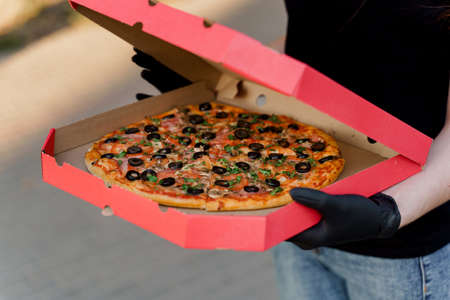 Pizza with salami and cheese in cardboard box. Safety delivery in black medical gloves from restaurant. Quarantine for stop coronavirus covid-19 版權商用圖片