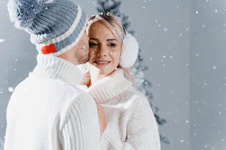 Happy young couple hugs and smiles and snow falls near christmas trees at the eve of new year celebration in winter day. Smiley man and woman weared white pullovers love each other Stock Photo