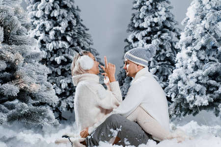 Couple seat on the snow and hug, kiss, and have fun each other. Winter love story before new year celebration. Waiting for christmas gift. Happy couple weared fur headphones, hats, white sweaters.