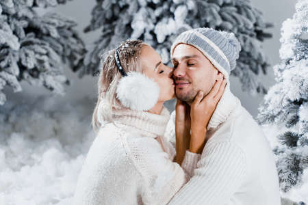 Winter love story with couple weared fur headphones, hats, white sweaters. Happy young couple hugs and kiss near christmas trees at the eve of new year celebration in winter day.