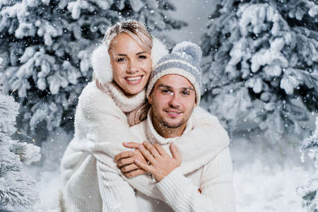 New year love story. Couple kisses and hugs. People weared wearing fur headphones, hats, white sweaters. Happy young couple hugs and kiss near christmas trees in winter day.