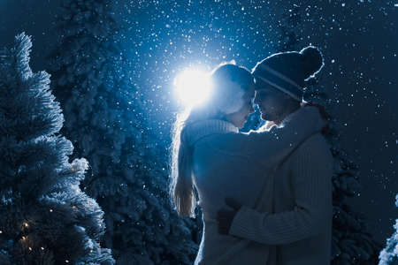 Falling snow and kisses with falling snow and dark blue background. Happy young couple weared white pullovers. hugs and kiss near christmas trees at the eve of new year celebration in winter day Stock Photo