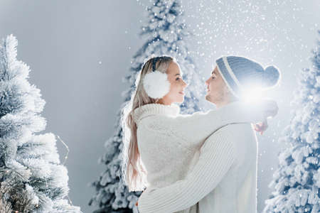 Falling snow and kisses. Happy young couple close-up hugs and kiss near christmas trees at the eve of new year celebration in winter day. Smiley man and woman weared white pullovers love each other