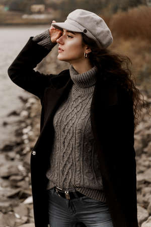 A beautiful girl in a black coat and a gray woolen cap near the lake. Traveling in your country