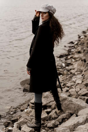 Attractive girl tourist travels around her country and thinks about end of quarantine of coronavirus covid-19. Young woman with curly hair looks at the lake and dreams about her life.