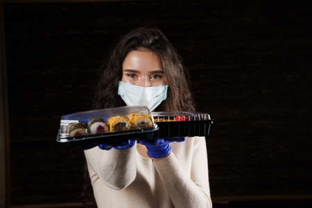 Girl sushi courier in medical mask with 2 boxes. Sushi set in box healthy food delivery service by car. Japanese cuisine: rolls, soy sauce, wasabi. 版權商用圖片