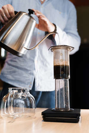Aeropress coffee close up alternative making by barista in the cafe vertical photo. Barista pours hot water in pot for making aeropress coffee with special device. Advert for cafe, restaurants.