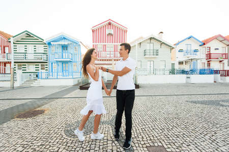 Young couple stays in tango pose and looks each others in Aveiro, Portugal near colorful and peaceful houses. Lifestyle. Having fun, laughs, smiles. Tourism trip after quarantine in Portugal