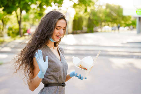 Young surprised girl with curly hair in medical gloves and mask holds wok in box in hands and smiles. Udon noodles in white box delivery. Advertise for Japanese restaurant at quarantine covid 19