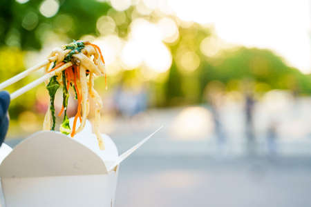 Closeup udon noddles on blurred background gets out of the white box. Advertise for Japanese restaurant delivery. Stay at home and eat udon noodles with tempuru, shrimps, soy sauce. Safe delivery