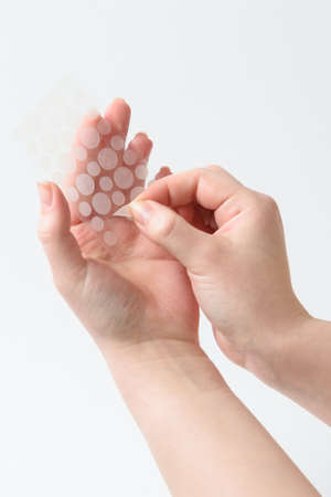 Round patches for acne and wrinkles on the hands on a white background. Acne and wrinkle patches for facial rejuvenation. Facial cleansing cosmetology. Reklamní fotografie