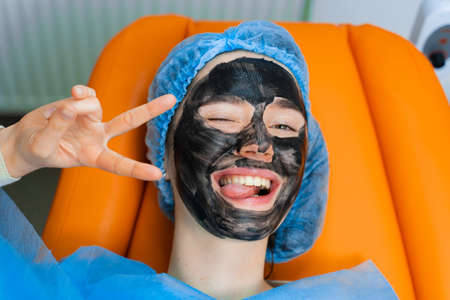 Black mask on girl face for carbon peeling. Dermatology and cosmetology. Using surgical laser.