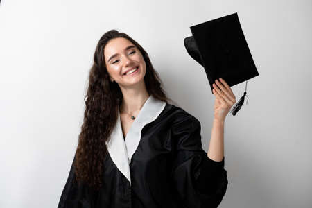 Graduate girl with master degree in black graduation gown and cap on white background. Distance learning online. Study at home. Graduation from college.