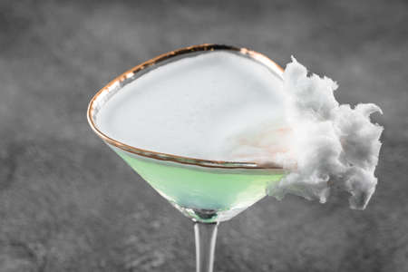 Green alcohol cocktail in a glass decorated with cotton candy on gray background