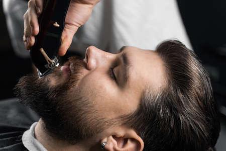Beard shaving in barbershop. Barber with dreadlocks trim handsome bearded man Stock Photo