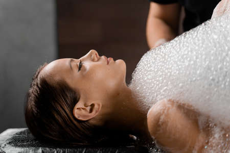 Close-up foam peeling massage for model in spa. Relaxation in Turkish hammam. Banque d'images