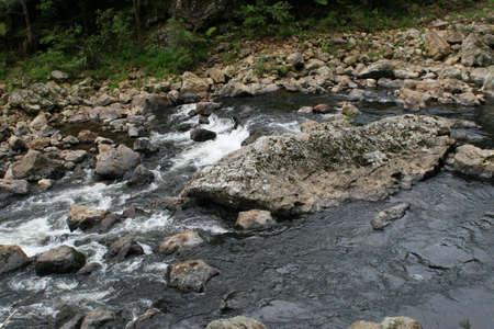 exultation: Slow moving calm river flowing over rocks
