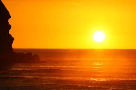exultation: Last rays of a gorgeous sunset at Piha beach Stock Photo