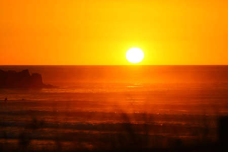 exultation: Last rays of a gorgeous sunset at Piha beach Stock Photo