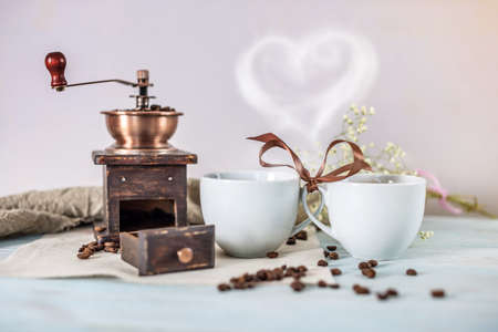 ?ouple of cups of fresh, fragrant black coffee are tied with a brown ribbon. Steam comes out of the mugs and forms a heart. Romantic breakfast, cozy morning