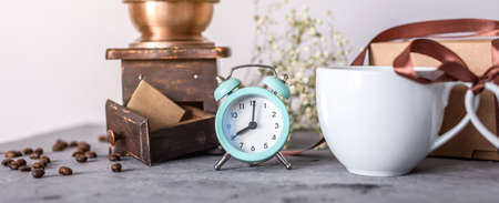 A Cup of fragrant morning coffee, an alarm clock and a retro coffee grinder on the table. Start a good and productive day