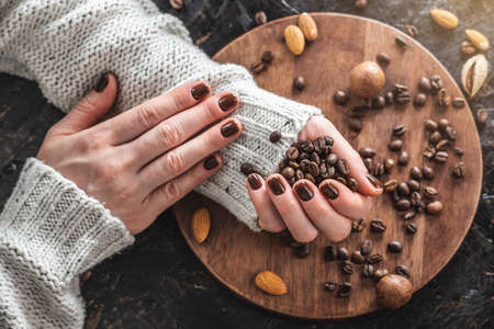 Beautiful neat female hands with nails covered with brown nail polish hold aromatic roasted coffee beans. The concept of a fashionable and stylish coffee manicure Standard-Bild