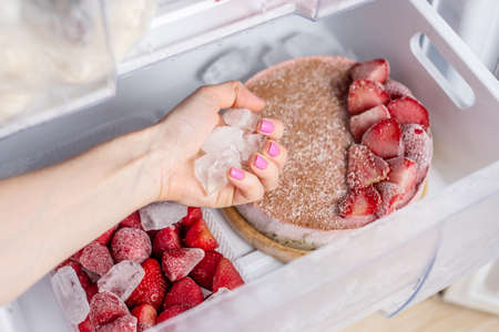 Frozen strawberry cake and strawberries in the freezer drawer of the fridge. Concept of the convenience of frozen food and to save time.