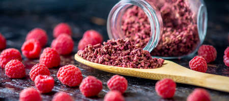 Freeze dried raspberries in a glass jar and a wooden spoon on a black background. Concept of berry storage types. Banque d'images