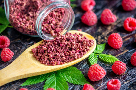 Freeze dried raspberries in a glass jar and a wooden spoon on a black background. Concept of berry storage types. Stock Photo