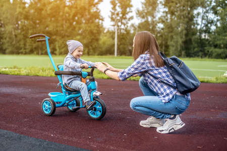 Happy toddler boy is successfully going to his mother on a children's tricycle. Concept of learning to ride a bike and having fun with your family.