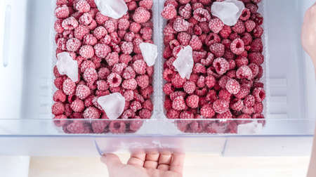 Containers with frozen raspberries in the freezer of the fridge. Concept of frozen food, long term storage products.