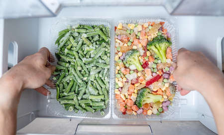 Hands are taking a container of frozen vegetables from the freezer of the fridge. Concept of storing ready dish and saving time. Foto de archivo