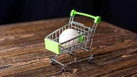 White raw fresh eco egg in a shopping cart on a wooden background. Concept of online purchasing of farm products delivery.