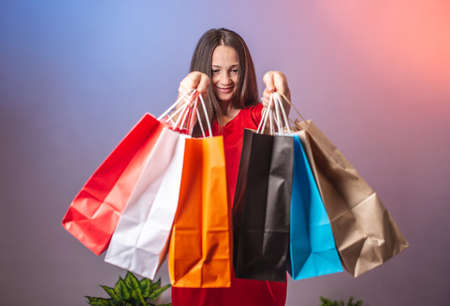 Young woman in a red dress is holding a lot of multicolored paper bags with purchases. Concept of shopping and sales. Blue and pink background.