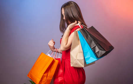 Young woman in a red dress is holding a lot of multicolored paper bags with purchases. Concept of shopping and sales. Blue and pink background. Stock fotó - 155446537