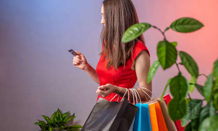 Young woman in a red dress is holding a lot of multicolored paper bags with purchases and credit card. Concept of shopping and sales. Stock fotó