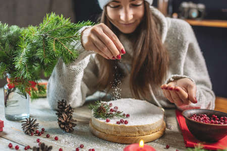 A woman is decorating a white mousse festive cake, sprinkling it with coconut flakes imitating snow. Concept of Christmas and New Year.