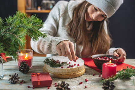 A woman is decorating a white mousse festive cake with red berries sprinkled with coconut flakes that imitating snow. Christmas and New year concept.