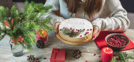 Woman is holding a festive white mousse cake covered with coconut flakes imitating snow and decorated with red berries, cones and fir branches. Concept of the New year and Christmas.