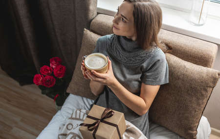 A young beautiful girl is sitting on the bed by the window with a gift box and flowers and enjoying coffee on a festive morning. Concept of a nice start to the day with a cup of cappuccino. Stock Photo
