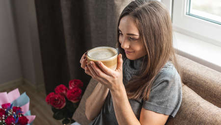 A young beautiful girl is sitting on the bed by the window and enjoying coffee. Concept of a nice holiday morning with a Cup of cappuccino and a good mood. Stock Photo