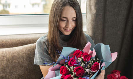 Happy young woman with a beautiful bouquet of fresh roses at home. Concept of a holiday, romance, good mood. Zdjęcie Seryjne