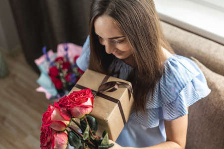 Happy young woman with a beautiful bouquet of fresh roses and a gift box in her hands at home. Concept of a holiday, romance, good and cozy mood in birthday. Zdjęcie Seryjne