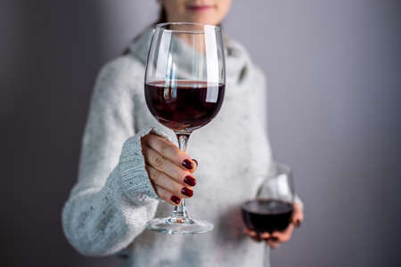A woman in a white sweater is holding two glasses of red wine and holding out one of them. Close up. Stock fotó