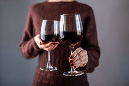A woman in a brown sweater is holding two glasses of red wine and holding out one of them. Close up.